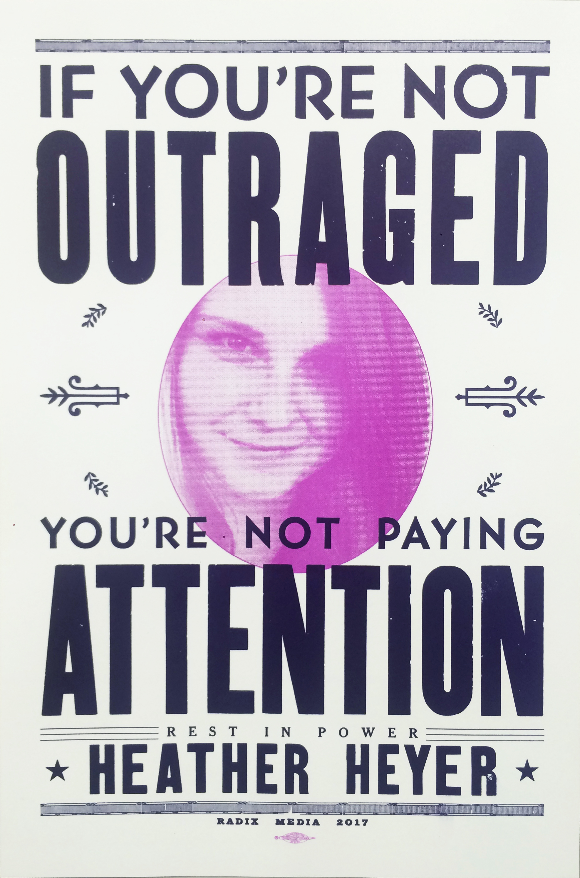 "Poster with an image of Heather Heyer and the words ""If you're not outraged, you're not paying attention""."